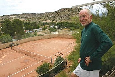 Rick Champion looks over his clay tennis court from a terrace outside of his Cottonwood home. Champion built the home and the tennis court himself.