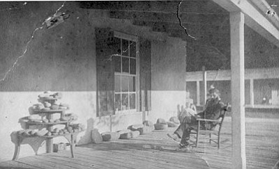 Dr. Mearns on his porch with collection of pots.