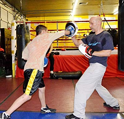 <b>Javier Mestas</b> hits the mitts with Skip, a GC trainer, Monday at GC gym. VVN/Sean Morris