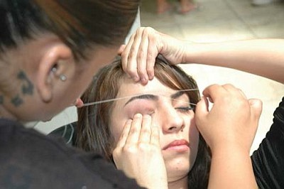 Xenia Perez uses thread to pluck hairs from the eyebrows of 15-year-old Jasime Murillo at a kiosk at Desert Sky Mall in Phoenix. The Arizona Board of Cosmetology has now agreed to halt its efforts to require practitioners to be trained and licensed as cosmetologists.  (Capitol Media Services file photo by Howard Fischer)