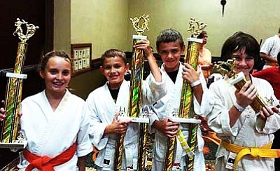 Kenya Roberts, Jesse Roberts, Gage Roberts and Aaron Rhodes stand with the trophies from the Phoenix Summer Showdown. Photo courtesy of KC's Family Tae Kwon Do