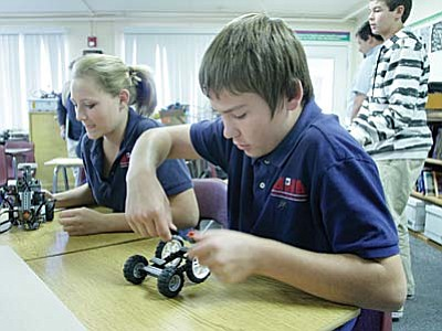 American Heritage Academy eighth grade students Delaney Musselman and Daniel McInnis, from left, build a robotic vehicle. VVN/Bill Helm