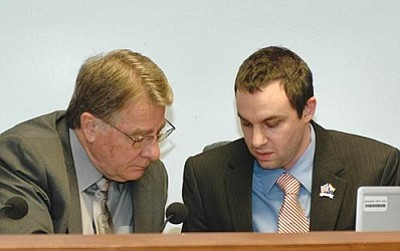 Sen. Steve Yarbrough and Rep. J.D. Mesnard confer about proposed changes in state income taxes. The special panel Mesnard is chairing is recommending collapsing income tax brackets, future indexing -- and moving toward a single rate. (Capitol Media Services photo by Howard Fischer)
