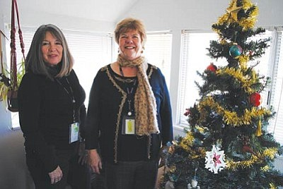 Janet Conchy and Carol Quasula in The Loft's small living room. They are getting ready for their yearly Christmas party.