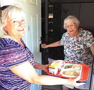 Volunteer Cyndi Collingwood, left, brings a meal to Alene Wood through the Meals-on-Wheels program. VVN photo by Tom Tracey