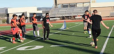 Head Coach Calvin Behlow (Middle) gives instruction to his players during a drill in practice on Wednesday. The boys will get a preseason tune-up on Friday when they host Joy Christian at 5 p.m. at home. (Photo by Greg Macafee)