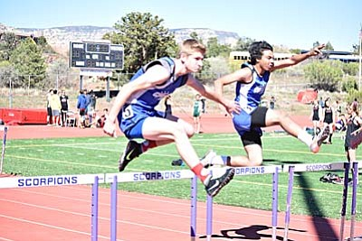 Nate Schultz and another Camp Verde athlete participate in the 110 meter hurdles earlier this season at the Sedona Friendship Meet. Schultz is one of three automatic qualifiers for the Camp Verde Cowboys, qualifying in the High Jump event. (Photo by Greg Macafee/VVN)