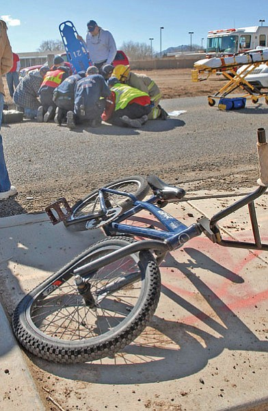 Special to the Review/Jo.L. Keener<br> Chino Valley Fire District (CVFD) crews prepare to take D.J. Parker, 12, to the Yavapai Regional Hospital in Prescott, after a car hit him on his bicycle on east Road 2 North, just past Safeway. D.J. suffered a broken leg and broken collarbone. The boy is son of CVFD Capt. Danny Parker, who was not working at the time. Crews quickly notified Parker and his wife of the accident. Witnesses said the boy darted out into traffic.