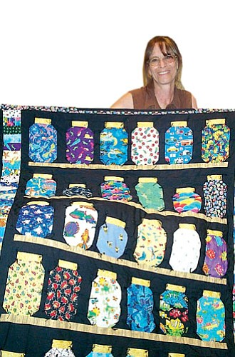 """Review/Diane DeHamer<br> Above, Robin Peterson of Chino Valley, shows a quilt she made called, """"Things You Can Put In A Jar,"""" and top left, sofa pillows, and bottom left, one of her a quilt tops, and at right, a """"Stained Glass"""" quilt."""