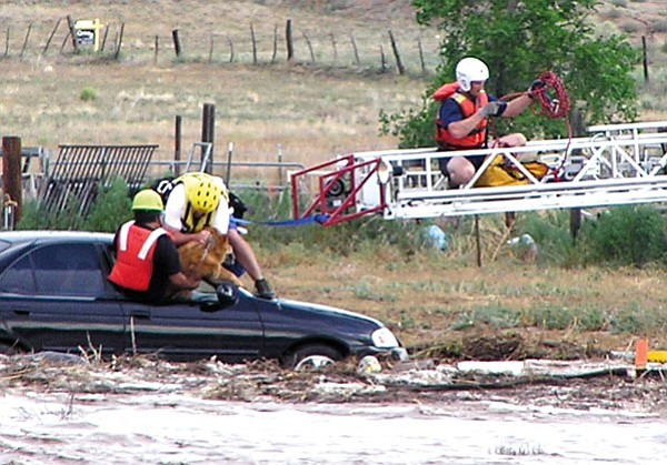 Courtesy photo/Tammy Imperia<br> Chino Valley and Prescott fire personnel rescue crews remove a dog and a man (in black shirt) from a car stuck in flood water and debris Sunday at 3:30 p.m.  at the bridge at Road 2 North and Porcupine Pass.