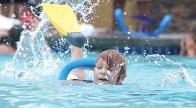 The Daily Courier/file photo<br> Chance West keeps an eye on his opponents and kicks hard in the Wacky Water Olympics Water Gear Relay at the Chino Valley Aquatic Center.