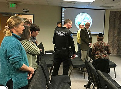 A Chino Valley Police officer escorts Rabbi Adele Plotkin (right) out of council chambers after she protested the Christian prayer that Mayor Chris Marley gave at Tuesday's meeting. (Ken Sain/Review)