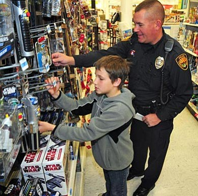 Bret Soldwedel/The Daily Courier, file<br>Prescott police officer Ryan Ehlert helps a child choose gifts for his family during Shop with a Cop last year at the Kmart in Prescott Valley.