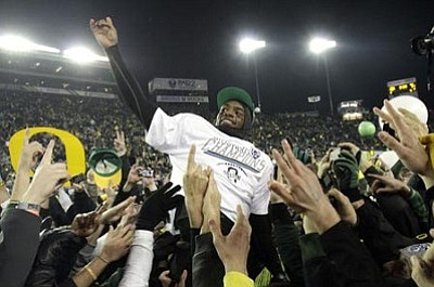 Oregon quarterback Darron Thomas is lifted by cheering fans after winning their NCAA Pac-12 Championship game against UCLA in Eugene, Ore., Friday, Dec. 2, 2011. Oregon won 49-31.(AP Photo/Don Ryan)