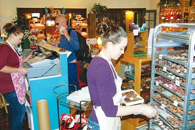Jason Soifer/The Daily Courier<br> Ashley Moser, manager at Pralines of Prescott, assembles a one-pound box of assorted chocolates – the most popular assortment at the store in the Bashford Courts shopping center.
