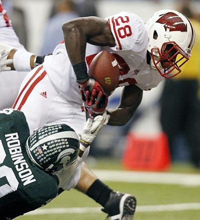 Wisconsin's Montee Ball goes in for a 6-yard touchdown run while being tackled by Michigan State's Trenton Robinson during the first half of the Big Ten conference championship NCAA college football game on Saturday, Dec. 3, 2011, in Indianapolis. (AP Photo/Michael Conroy)