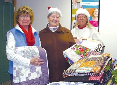 """Courtesy Home Instead Senior Care<br>Judy Lapp, left, and Chris Turner, right, of the Lonesome Valley Quilt Guild present Susan D. Abbott, center, owner of Home Instead Senior Care, with 22 handmade quilts to distribute to isolated seniors in need as part of the """"Be a Santa to a Senior"""" program."""