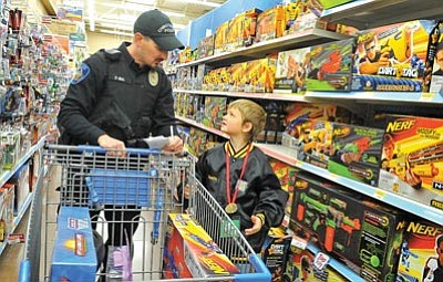 Matt Hinshaw/The Daily Courier<br>Bryce, 7, asks Chino Valley Police Officer Daniel Beal about the next gift to get for his family Saturday morning during the annual Shop with a Cop event at the Wal-Mart on Gail Gardner Way in Prescott.