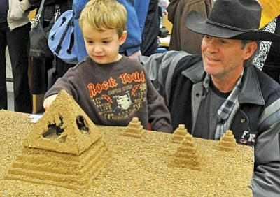Matt Hinshaw/The Daily Courier<br>Donald Grier and his son Shane, 3, check out a pyramid display during Prescott Mile High Middle School's 6th Grade class' Ancient Civlization Night this Wednesday in Prescott.