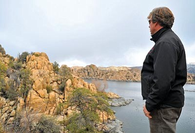 Matt Hinshaw/The Daily Courier<br>Chris Hosking, the City of Prescott's trails specialist, looks out over a piece of land at Watson Lake that would complete a trail circling the whole lake Wednesday afternoon in Prescott.