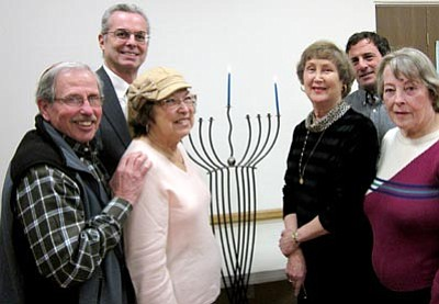 Courtesy photo<br>Rabbi William Berkowitz and congregants of Temple B'rith Shalom light the menorah to celebrate the first night of Chanukah, the Jewish Festival of Lights.