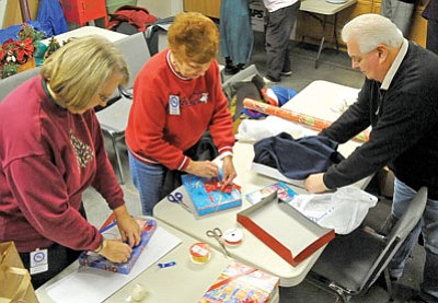 Matt Hinshaw/The Daily Courier<br>From left, Nancy Burgess, Elaine Schubert, and David Llewellyn members of the Prescott Antique Auto Club wrap gifts for residents at the Bob Stump VA Community Living Center Tuesday morning at their clubhouse in Prescott.