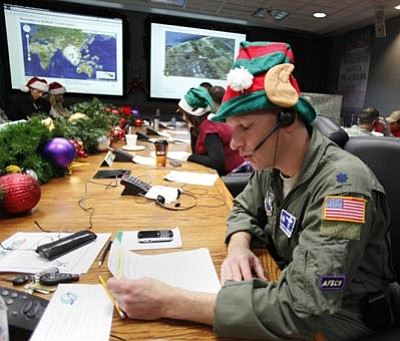 Ed Andrieski/The Associated Press<br> In this Dec. 24, 2010, file photo, Air Force Lt. Col. David Hanson of Chicago takes a phone call from a child in Florida at the Santa Tracking Operations Center at Peterson Air Force Base near Colorado Springs, Colo.