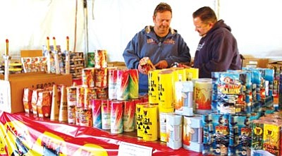 Lisa Irish/The Daily Courier<br> John Moore, left, who manages the Snap Fireworks stand in the Depot Marketplace parking lot in Prescott, talks with Prescott Fire Division Chief Eric Kriwer about some of the fireworks for sale at his stand on Tuesday afternoon.