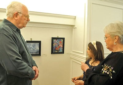 Matt Hinshaw/The Daily Courier<br>Tanya Tuttle, 9, talks with her grandparents Dexter and Barbie Tuttle about one of her paintings Friday evening during the STEPS Children's Art Show at 'Tis Art Center Mezzanine Gallery in downtown Prescott.