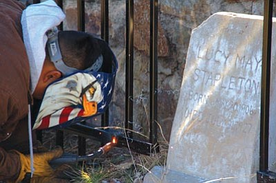 Joanna Dodder/The Daily Courier<br> Ward Fence employee Joel Gonzales uses a welding tool to cut out the wrought-iron fence around a gravestone at Citizens' Cemetery in Prescott last week.