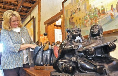 "Matt Hinshaw/The Daily Courier<br> Cindy Gresser, managing director of the Smoki Museum, adjusts Doug Hyde's bronze sculpture ""Honor Song"" Wednesday afternoon."