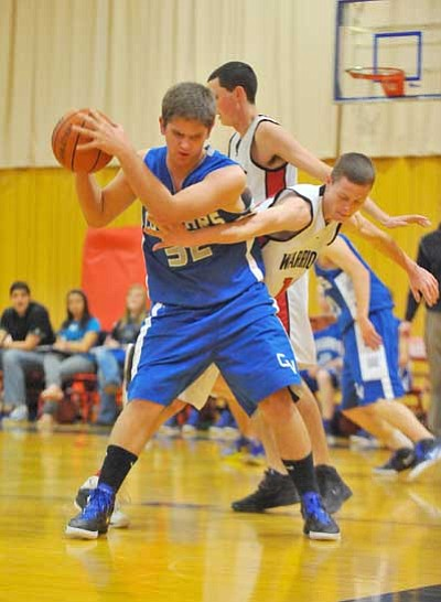 Matt Hinshaw/The Daily Courier<br> Chino Valley's Branden Redfern, 32, makes a move towards the hoop while Orme's Kaleb Johnson, 10, blocks him Tuesday night at the Orme School in Mayer.