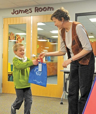 Matt Hinshaw/The Daily Courier<br>Discovery Gardens 5-year-old teacher Judy Ely hands Jackson Waara, 5, a book bag at the Prescott Public Library during the Raising a Reader program by First Things First Thursday afternoon in Prescott.