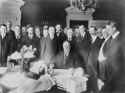 Ralph Cameron stands in the foreground at the right shoulder of President William Howard Taft as he signs the document making Arizona the 48th state admitted to the Union on February 14, 1912.<br>  Sharlot Hall Museum/Courtesy photo