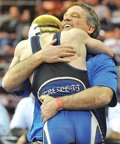 Matt Hinshaw/The Daily Courier<br /><br /><!-- 1upcrlf2 -->Prescott High 120-pound wrestler Mike Burkeen receives a big hug from coach Eric Koehler after taking third place Saturday afternoon during the Division II High School State Wrestling Championship tournament at Tim's Toyota Center in Prescott Valley.