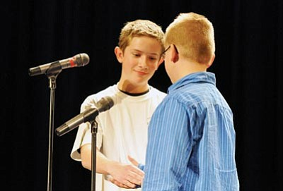 Heidi Dahms Foster/Courtesy photo<br> 2012 Yavapai County Spelling Bee winner Daxton Bryce, a Granite Mountain Middle School seventh-grader, shakes the hand of runner-up James Hanson, a Chino Valley Del Rio Elementary School fifth-grader, after the two spelled off in the final round of the bee at Prescott High School's Ruth Street Theater on Wednesday.