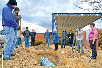Matt Hinshaw/The Daily Courier<br> Students and teachers watch as Prescott High School Principal Totsy McCraley throws the first shovelful of dirt onto the Prescott Unified School District time capsule at PHS Wednesday afternoon.