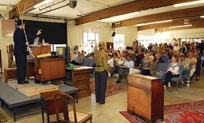 Kirk Vogel, auctioneer for  Batterman's Auction & Gallery, works to sell properties during a Saturday auction at the old McIlvain building on Gurley Street. File photo/ The Daily Courier