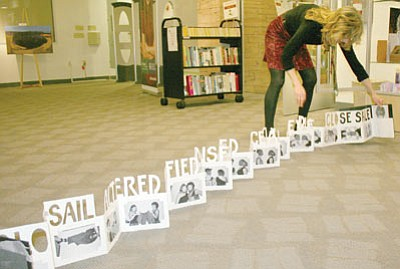"Sue Tone/Courtesy photo<br>Book artist Linda Illumanardi extends her book ""Altered"" about a pair of pants her daughter owned, across the YC Library floor."
