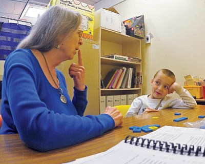 Matt Hinshaw/The Daily Courier<br>Volunteer Reading Tutor Rennie Anderson works with Cannon Flores, 6, Thursday morning at Miller Valley Elementary School in Prescott.