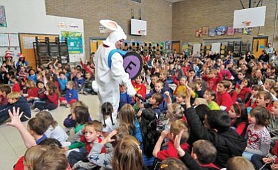 Matt Hinshaw/The Daily Courier<br> Lincoln Elementary School Principal Teresa Bruso, dressed in a bunny costume, holds a  microphone for one of her students to answer a question about famous bunnies Friday  morning during their Read Across America celebration in Prescott.
