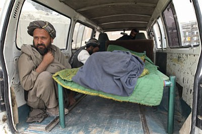 "Allauddin Khan/The Associated Press<br>An Afghan man sits in the back of a bus with the body of a person who was allegedly killed by a U.S. service member in the Panjwai, Kandahar province south of Kabul, Afghanistan, Sunday. Afghan President Hamid Karzai says a U.S. service member has killed more than a dozen people in a shooting including nine children and three women. Karzai called the attack Sunday ""an assassination"" and demanded an explanation from the United States."