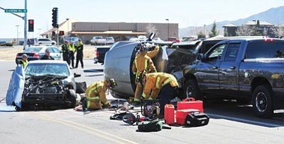 Les Stukenberg/The Daily Courier<br> Central Yavapai firefighters work to free one of the victims in this three-vehicle collision at the intersection of Centre Court and Glassford Hill in Prescott Valley Tuesday afternoon. Although there was heavy damage to all three vehicles, no one was seriously injured in the collision.