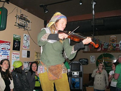 Ken Hedler/The Daily Courier<br /><br /><!-- 1upcrlf2 -->Maggie Dewar of the Mural Mice plays the violin atop a pool table at Coyote Joe's during a downtown Prescott power failure Saturday night.<br /><br /><!-- 1upcrlf2 -->