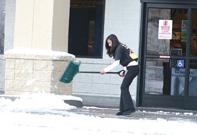 Matt Santos/Courtesy<br>Melinda Jordan shovels snow from the entrance of the Safeway store Sunday in Chino Valley after an overnight storm covered the town with several inches of snow.