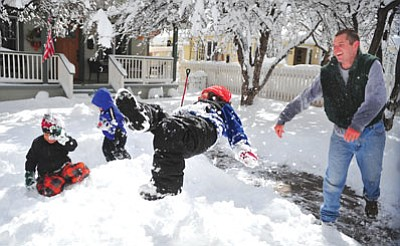 Les Stukenberg/The Daily Courier<br>Travis Newby tosses next door neighbor Cash Scarpignato into a snow bank on March 19 after an early spring storm dumped up to 12 inches of snow around the tri-city area.