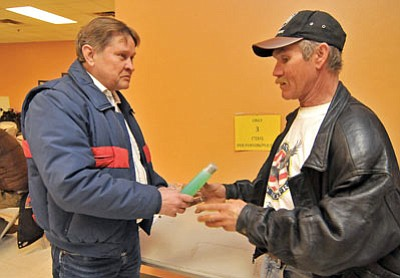 Matt Hinshaw/The Daily Courier<br> Joe Gatens, Outreach Coordinator for the United States Veterans Initiative, hands Army veteran Lawrence Nobbs a bottle of shampoo Tuesday morning at the Salvation Army in downtown Prescott. Gatens hands out toiletries every Tuesday morning to homeless vets.