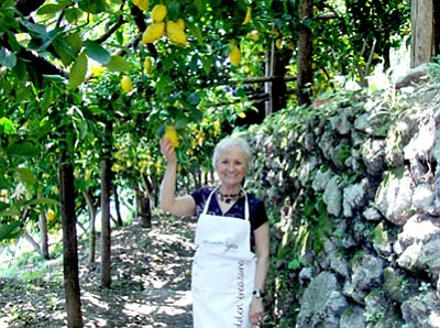 Courtesy photo<br>Peg Rhodes poses under lemon trees at Amalfi Cooking School.