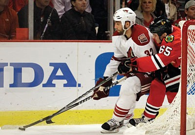 Nam Y. Huh/The Associated Press<br> The Coyotes' Michal Rozsival (32) controls the puck against Blackhawks' Andrew Shaw (65) during Game 6 of the first-round series Monday in Chicago.