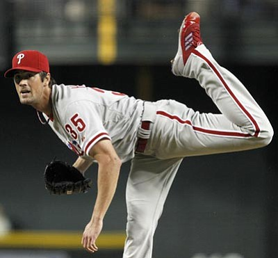 Philadelphia Phillies' Cole Hamels watches for a call after he makes a pitch against the Arizona Diamondbacks during the first inning in a baseball game on Wednesday, April 25, 2012, in Phoenix. (AP Photo/Ross D. Franklin)